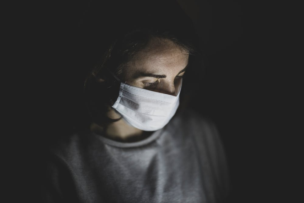 Person wearing a medical mask with dark background