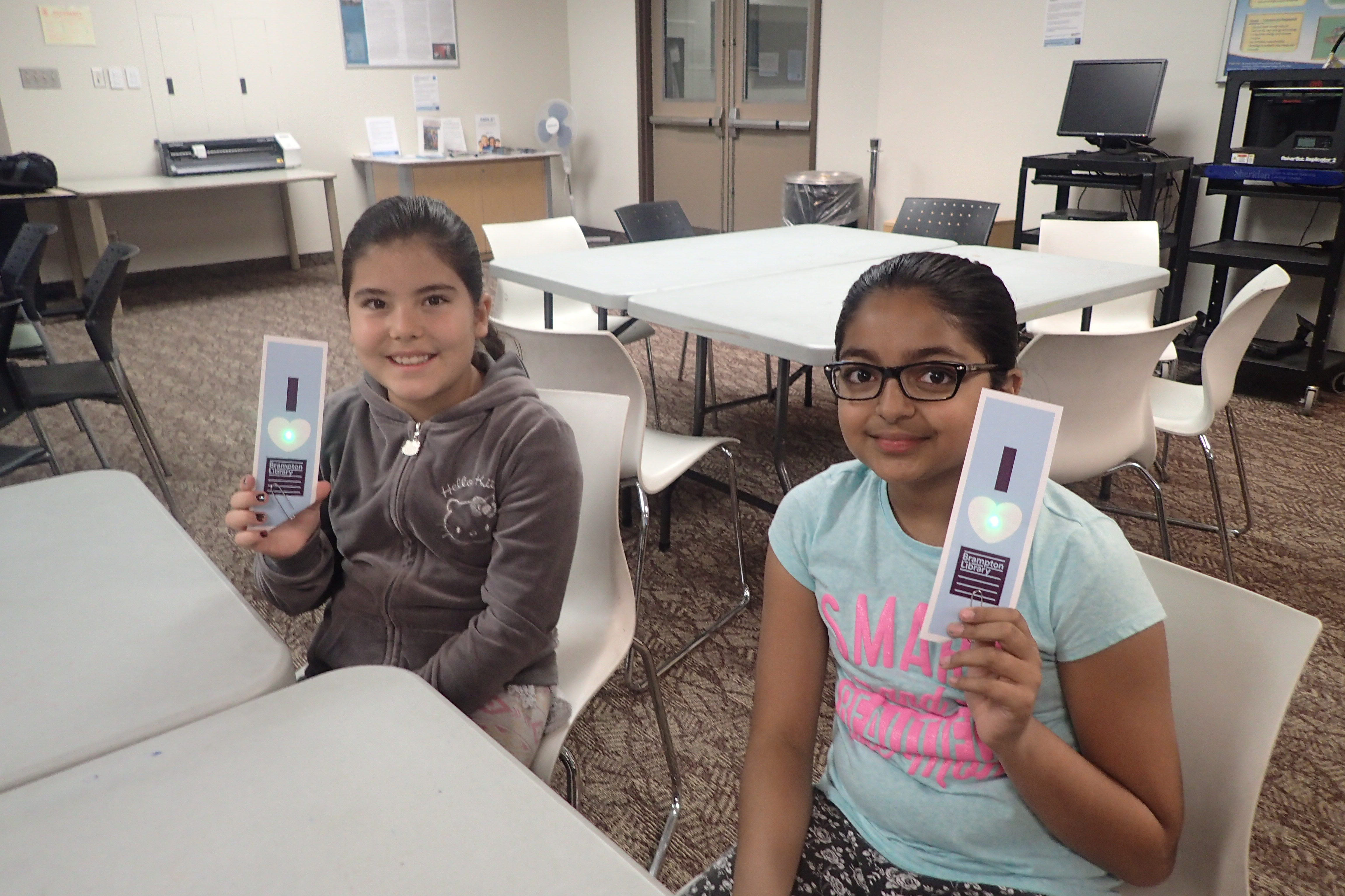 Two students holding Brampton Library bookmarks