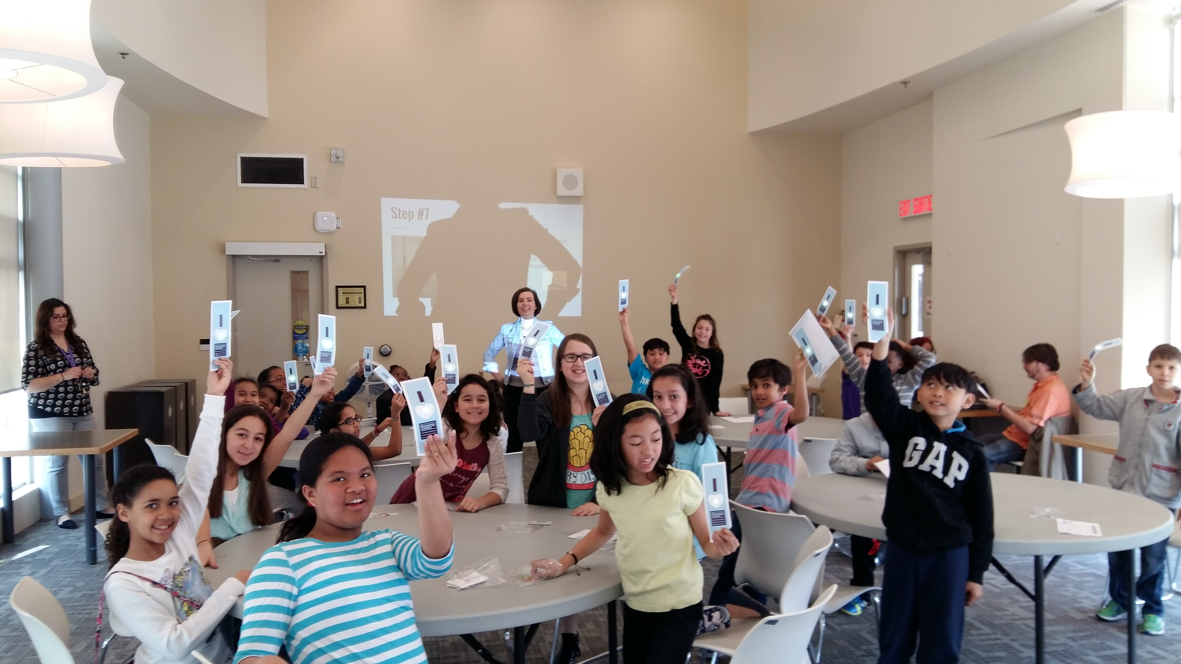A room of students celebrating and showing off their Brampton Library bookmarks