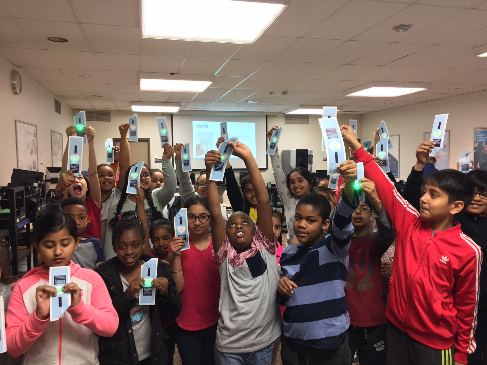 Students from Queens Street Public School holding up Brampton Library bookmarks