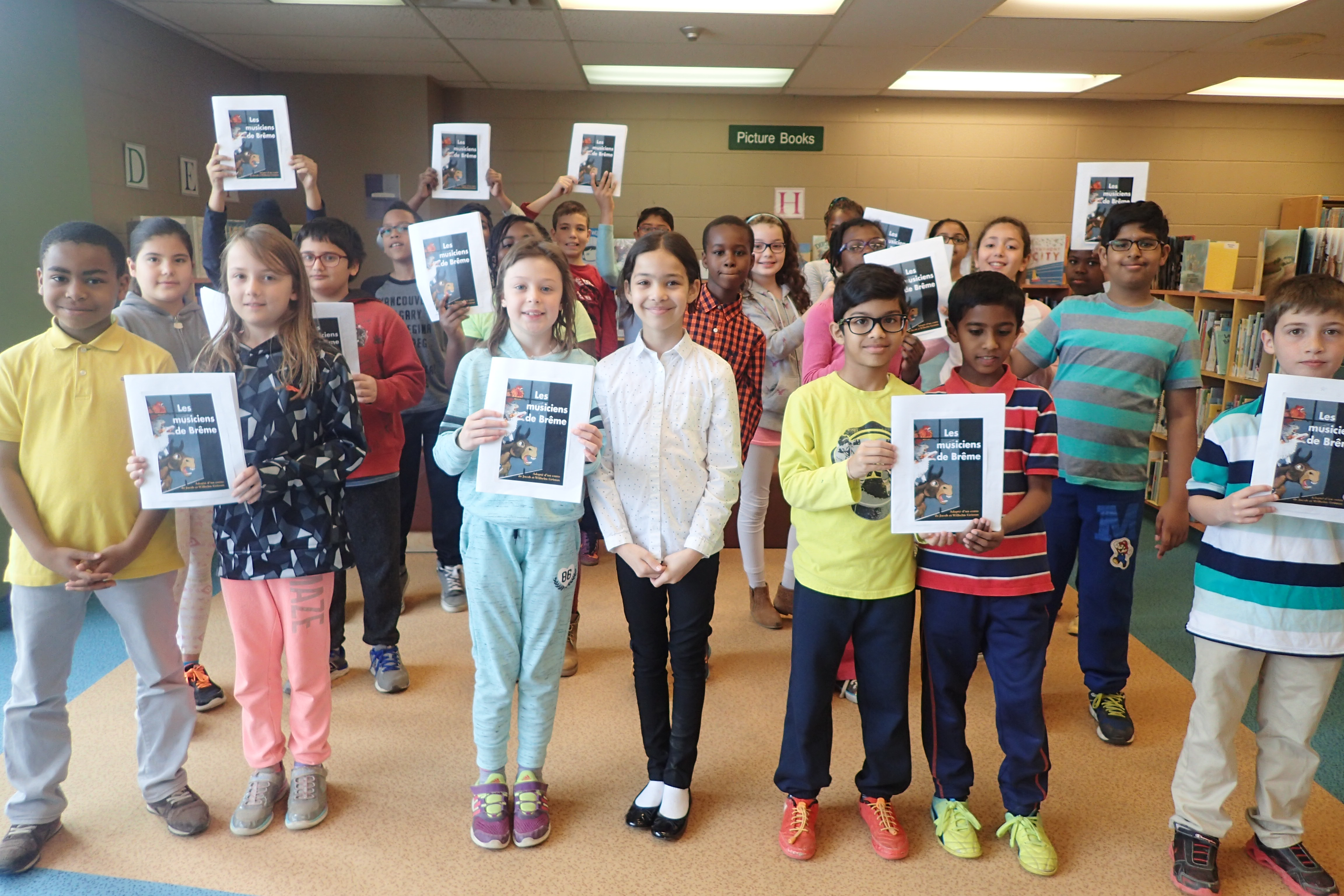 A group of students holding up French picture book titled 'Les musiciens de Brême'