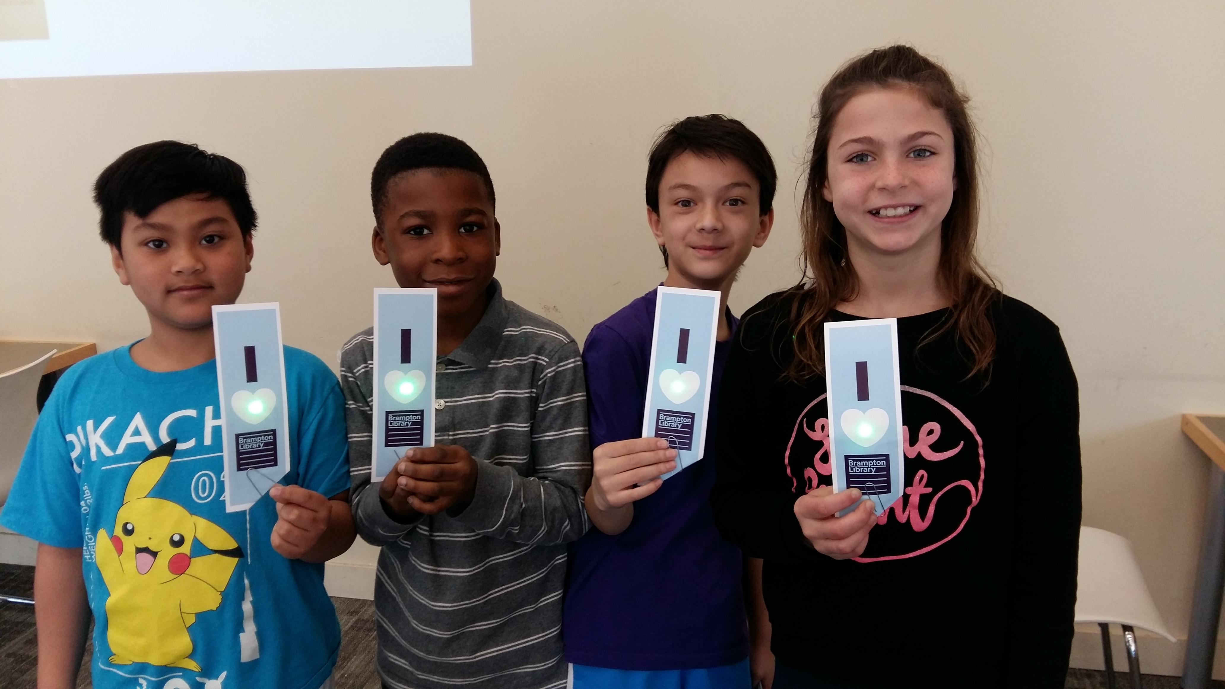 Four students holding Brampton Library bookmarks